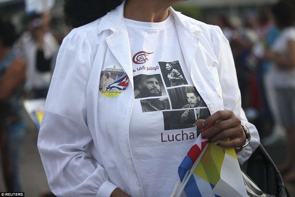 "A woman wears a t-shirt with images of Cuban former president Fidel Castro (L), revolutionary Vilma Espin (C), and Cuba's revolutionary hero Ernesto ""Che"" Guevara, beside a sticker with an image of Pope Francis during the first mass led by the Pope in his visit to Cuba"