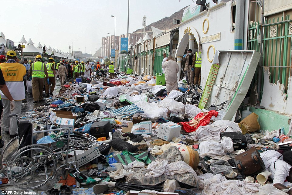 Saudi emergency personnel stand near bodies of Hajj pilgrims at the site where at least 717 were killed and hundreds wounded in a stampede