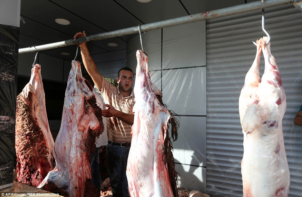 En masse: A butcher is seen hanging up carcasses of animals in a slaughterhouse in Ramallah in the West Bank region of Israel