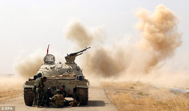 Kurdish Peshmerga soldiers hide behind a tank during a military operation against militants of Islamic State