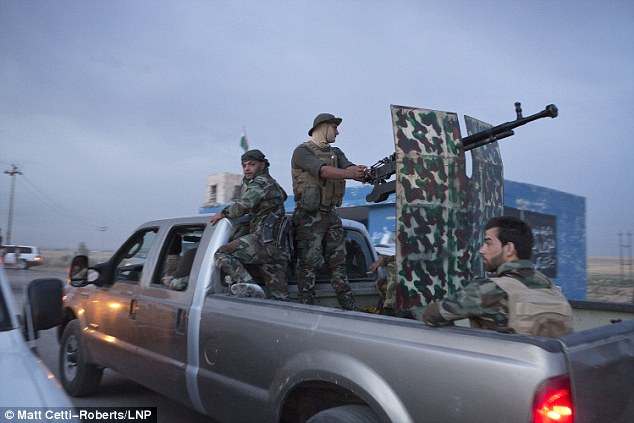 Kurdish peshmerga fighters travel in the back of a pickup truck armed with a heavy machine gun as they prepare to take part in an offensive to capture up to 11 villages from Islamic State militants near Kirkuk
