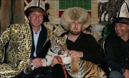 Colourful character: The former warlord (centre) seen in a bizarre social media snap cuddling a tiger which even has lead round its neck.the brutal reality of how Kadyrov maintains his grip on power has been glossed over by his social media skills and voracious appetite for posting on Instagram.