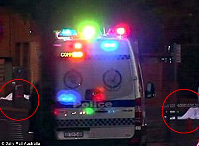 Both bodies (circled in red) were still on the scene at 11pm, draped in white sheets and just metres apart