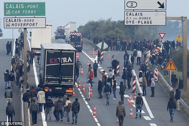 Amassing: Large numbers of migrants are pictured above outside a ferry port, advancing on lorries which have been stopped before reaching the UK