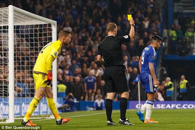 Referee Robert Madley shows Chelsea striker Falcao a yellow card for simulation at Stamford Bridge