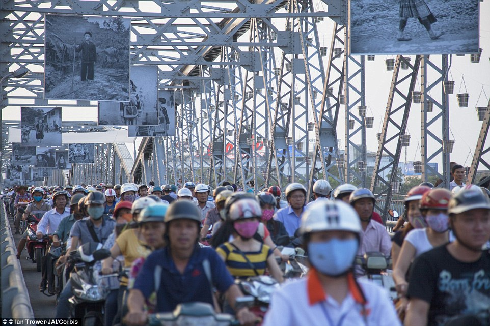 Not-so-easy riding: Commuters on motorcycles are pictured here crossing Trang Tien Bridge in Hue city, Vietnam