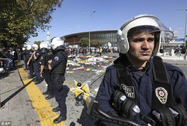 On edge: Turkish police officer stand guard shortly after the attack which killed over 97 people