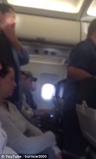 Passengers seated near the front of the plane can be heard defending the woman by 'booing'