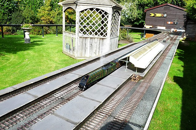 Realistic: A train stops at a station on the elevated 220ft model railway track in the back garden of John Judson's house in Little Bardfield, in Essex