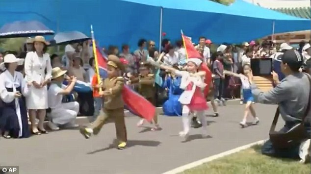 The young are encouraged to join the North Korean Children's Union and they take part in military parades (pictured)