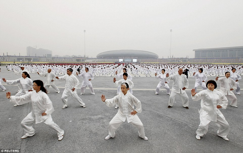 A huge group of Chinese people in white outfits doing Tai Chi in China
