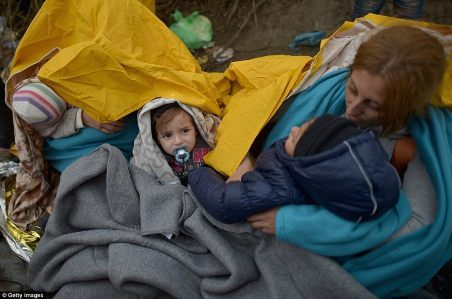 Keeping warm: In a sign of the worsening weather migrants close to the border between Serbia and Croatia were seen wrapped in blankets