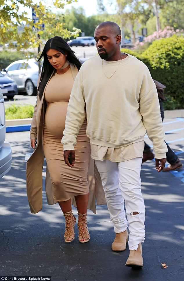 Due in December: The E! queen showed off her pregnant belly in a skintight beige dress with a long coat; Kanye matched her look in head-to-toe cream
