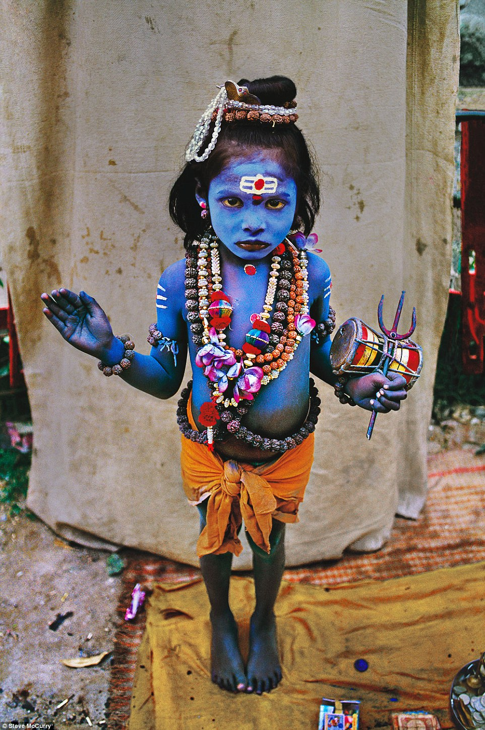 Haridwar, India, 1998. A young child dressed as the Hindu Deity Lord Shiva, often depicted in the colour blue, asks for alms at a religious festival