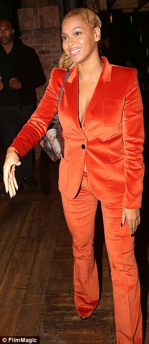Feeling all bright: The pop star was clad in an orange velvet pantsuit, with nothing but a bra underneath