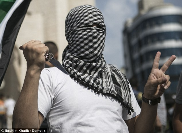Masked man: A Palestinian gives the v for victory sign whilst holding a knife during a demonstration in Gaza