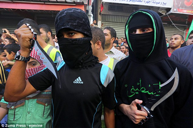 Palestinians hold knives during an an anti-Israel protest in Jabalia in the northern Gaza Strip