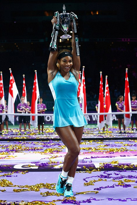 Serena Williams celebrates with the Billie Jean King trophy after defeating Romanian star Halep last October in Singapore