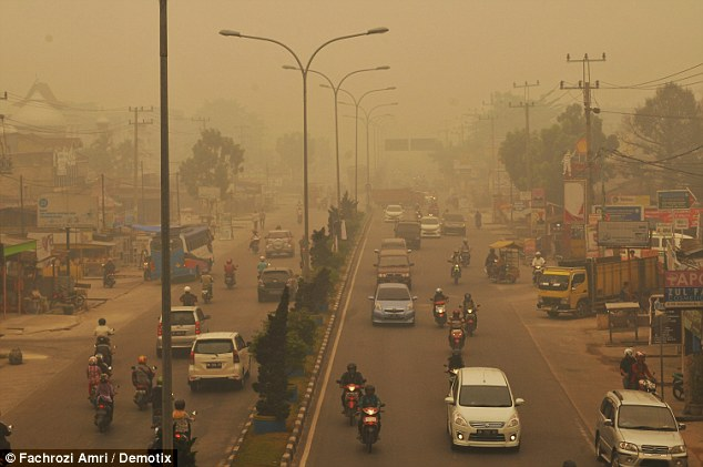Desperate evacuees took to their motorbikes in a desperate attempt to escape the acrid haze and choking pollution caused by thousands of forest fires in Indonesia