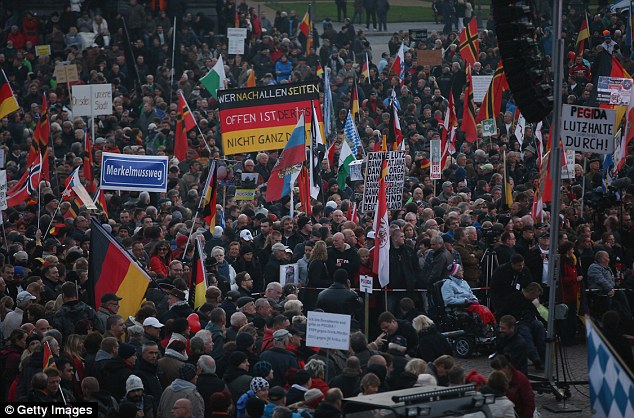Supporters of the Pegida movement - an acronym for 'Patriotic Europeans Against the Islamification of the West' - hold a rally in Dresden last week. Tensions have risen dramatically in recent months after Germany agreed to accept around one million refugees this year