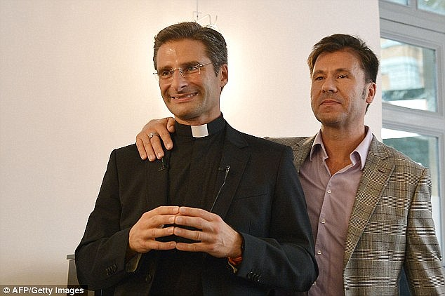 Polish priest Krzystof Charamsa (left) has accused the Catholic Church of making life 'hell' for millions of homosexuals after he was fired on the day he announced he was in a relationship with another man