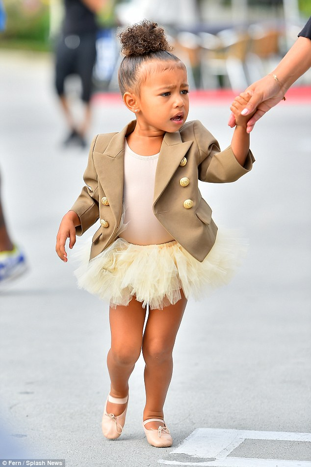 Couture cutie: Clearly mimicking her famous mother, she said the adorable words as she raises her hand, while wearing a tutu post ballet class and a taupe custom-made Balmain jacket