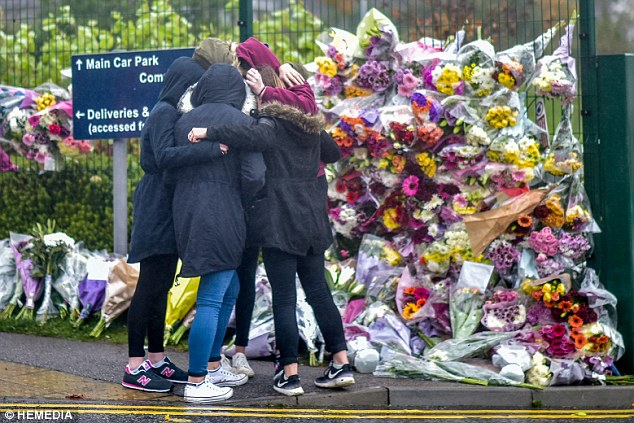 A group of girls console each other as they lay flowers in memory of Bailey Gwynne outside the school gate