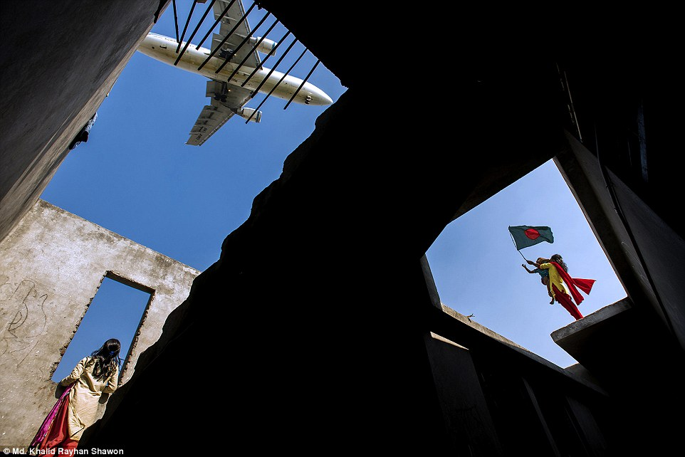 Open colour - Third Classified: Celebrating Victory by Md. Khalid Rayhan Shawon. Children inside and on top of a building under construction near the Dhaka International Airport runway watching the air craft landing while, at the same time, one of them is waving the national flag as to celebrate the Bangladesh's Victory Day on December 16
