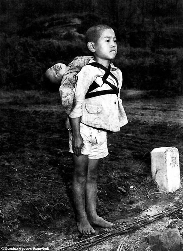Devastating: This crushing image by photographer Joe O'Donnell shows a young Japanese boy bringing his dead baby brother to a crematorium after the atomic bomb was dropped on Nagasaki in 1945