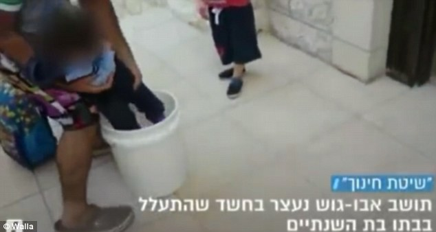 Punishment: The tiny child is squashed by her father into the plastic bucket as a young boy watches on