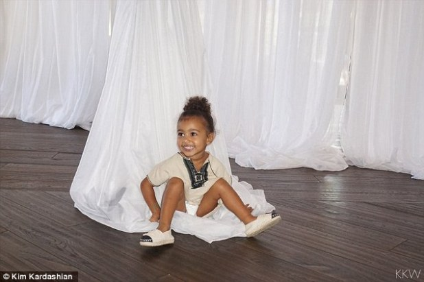 With her mini me: The pregnant Keeping Up With The Kardashians star's daughter North looked as cute as button as she sat in the white curtains that were hanging from the ceiling