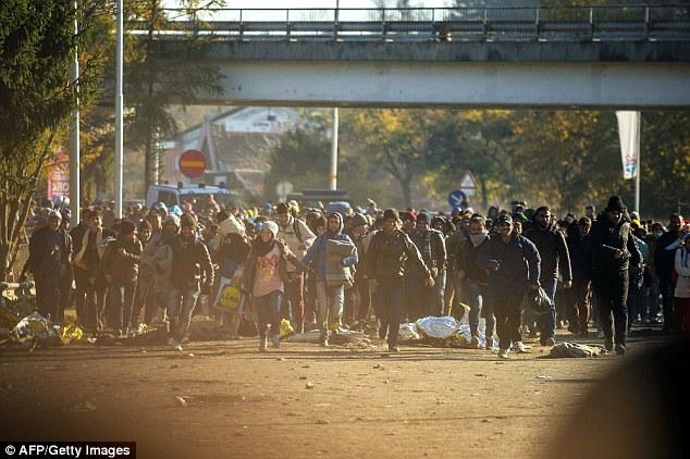 Los migrantes tomaron de las manos mientras cruzaban la frontera hacia Austria en el sol de invierno en la tarde del martes