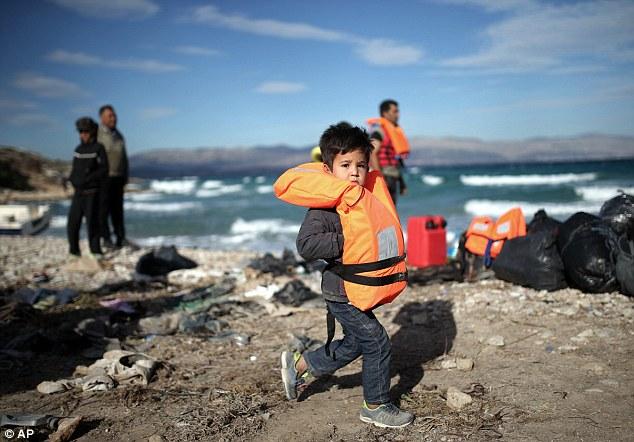 Un niño pequeño vestido con entrenadores, pantalones vaqueros y una chaqueta de paseos por la costa rocosa con las manos metidas en su chaleco salvavidas