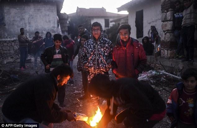 Un grupo de migrantes se inicia un incendio en un intento desesperado para mantenerse caliente mientras esperan en el complejo por un hueco en el tiempo