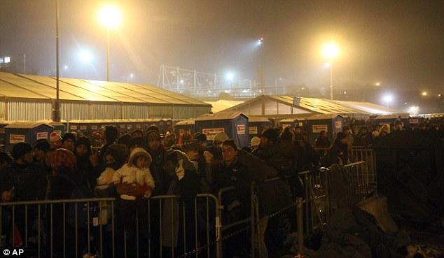 Los migrantes de pie delante de tiendas de campaña, ya que esperar para autobuses en Spielfeld después de cruzar la frontera entre Eslovenia y Austria