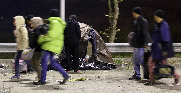Una tienda de campaña rodeada de escombros y basura fue erigido en el lado de la carretera y un pequeño bebé podría ser visto mira a escondidas de ella como otros migrantes caminaban por