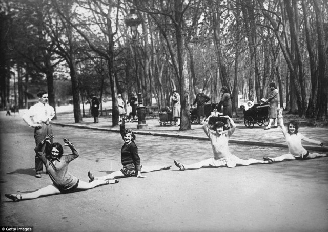 Practice makes perfect: Performers from the Moulin Rouge do the splits in the Bois de Boulogne Park, Paris in 1930