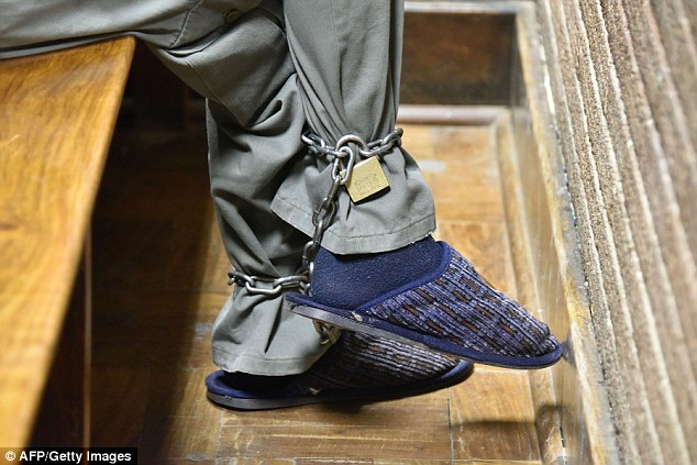 The cuffed feet of Frederiksen are pictured as he sits in the dock. He also faces counts of assault, bigamy, and production and distribution of child pornography