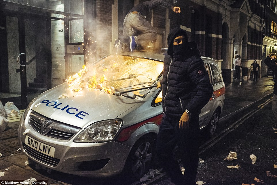 A police car was set on fire by an anti-capitalist demonstrator, who was wearing a Colmar ski jacket that cost hundreds of pounds