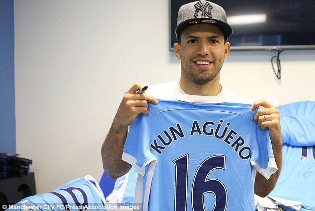 Sergio Aguero holds up a Manchester City shirt with his old No 16 on the back as he signs them for fans