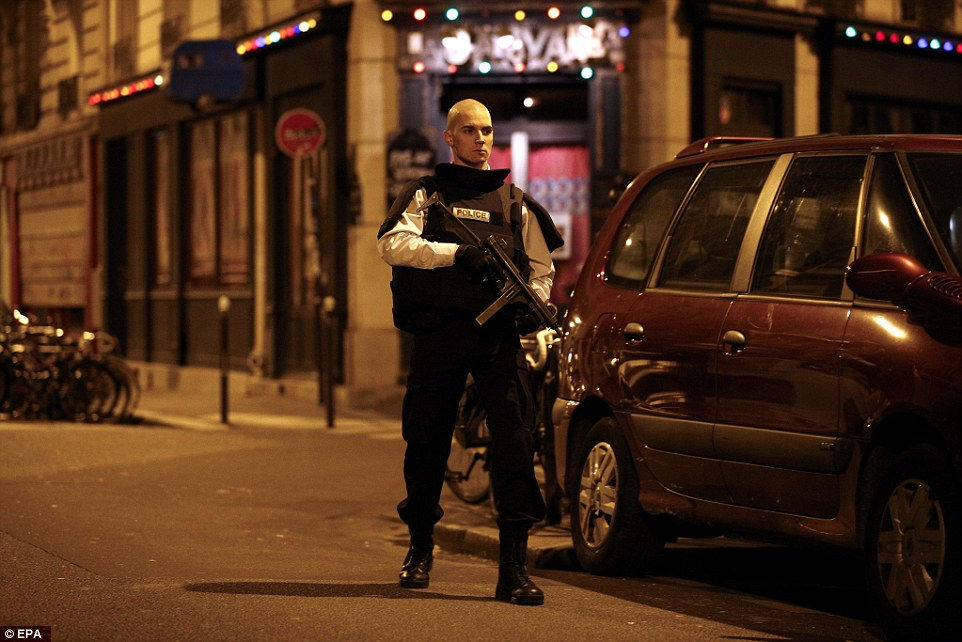On guard: A machine gun-wielding police officer stands to attention on a street near the scene of the restaurant shooting
