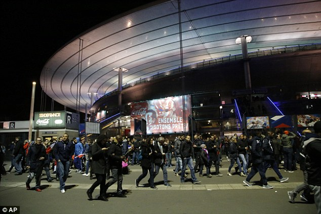 Police monitor the crowds as people are slowly evacuated from the stadium on Friday night, afraid of the violence outside the stadium