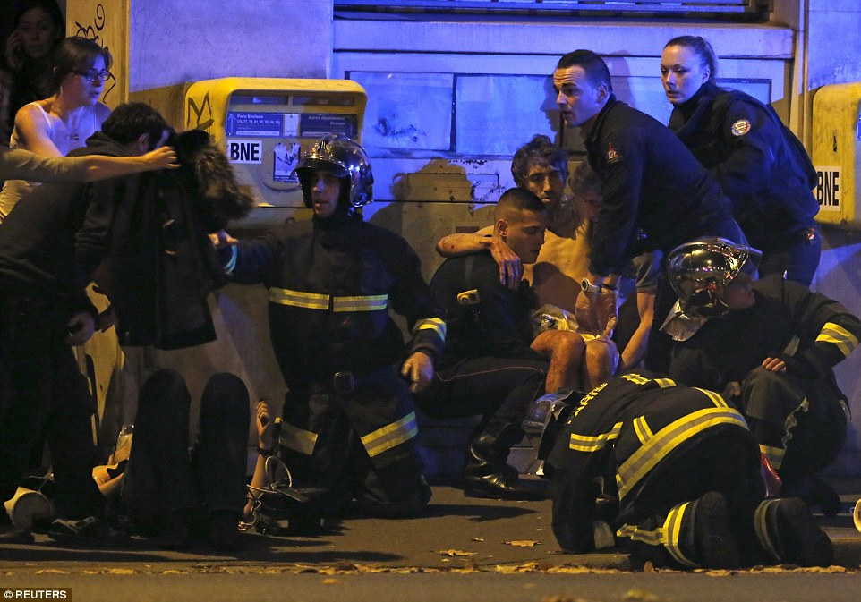 French fire brigade members help an injured individual near the Bataclan concert hall following fatal shootings in Paris