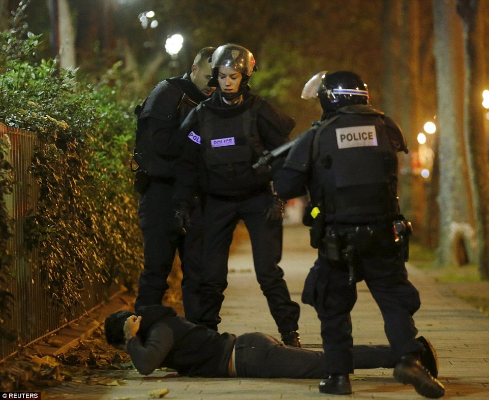 A man lies on the ground as French police check his identity near the Bataclan concert hall following a series of terror attacks in Paris