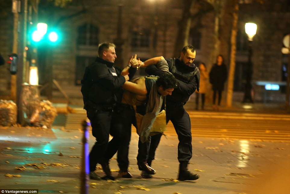 Handcuffed: A man is arrested by police near the Bataclan theatre where up to 100 concert-goers were massacred by ISIS militants in a night of terror on the streets of Paris. It is not know if this man was detained in connection with the attacks
