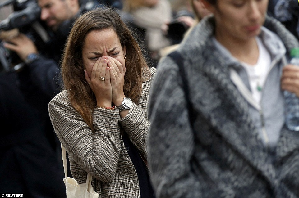 Shock: A woman breaks down in tears while visiting Le Carillon cafe, where around 14 people were killed in the terror attacks