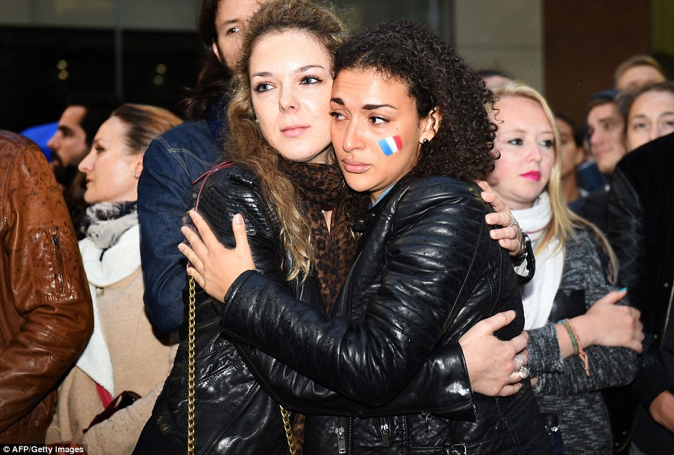 Mourners embrace at a vigil for victims of the Paris terror attacks as they prayed for the dead and searched for the missing