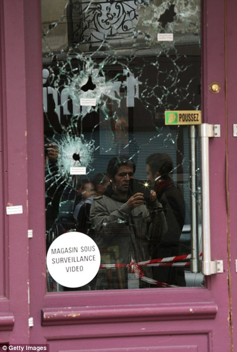 Bullet holes are seen through the glass door of the Casa Nostra Cafe after yesterday's terror attack