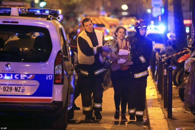 Rescue workers help a woman outside the Bataclan theatre in Paris where American band Eagles of Death Metal had been performing