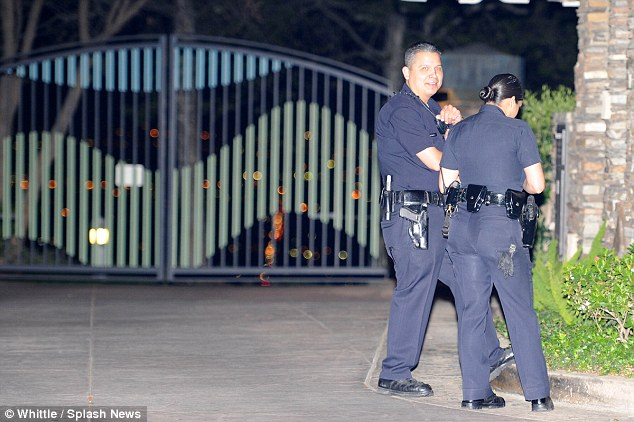 Police in front of Sheen's gated community Mulholland Estates. The 50-year-old star has been so paranoid that someone will reveal his sordid secrets, he has set up a security command post in his garage
